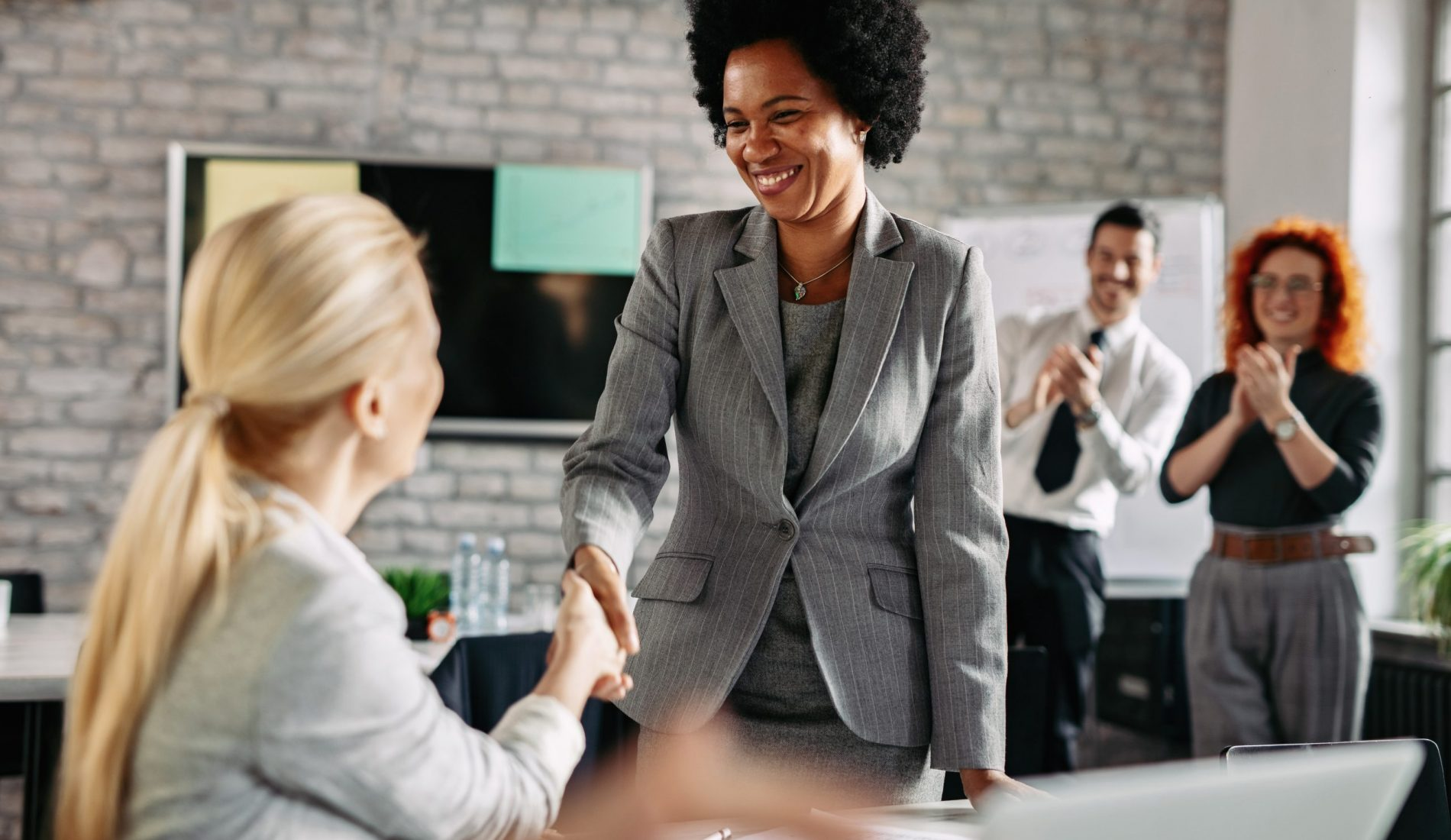 Two happy businesswomen shaking hands and congratulating to each other in the office while their colleagues are applauding. Focus is on Africa America businesswoman.